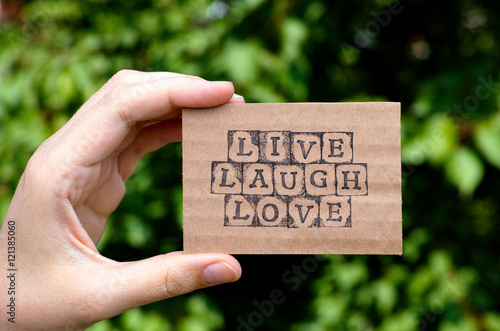 Woman hand holding cardboard card with words Live Laugh Love made by black alphabet stamps opposite green floral background Poster