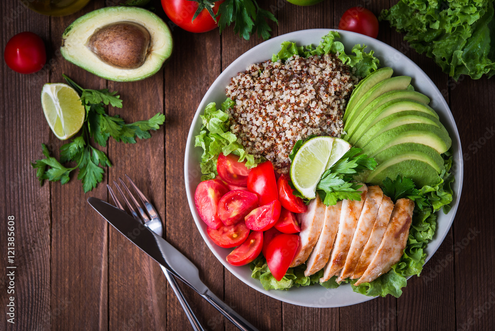 Fototapety, obrazy: Healthy salad bowl with quinoa, tomatoes, chicken, avocado, lime and mixed greens (lettuce, parsley) on wooden background top view. Food and health.