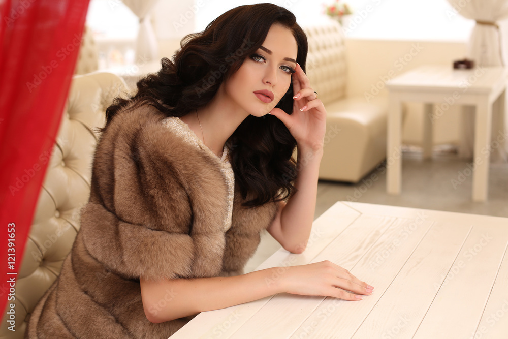 Fototapeta woman with dark hair in elegant clothes and luxurious fur coat