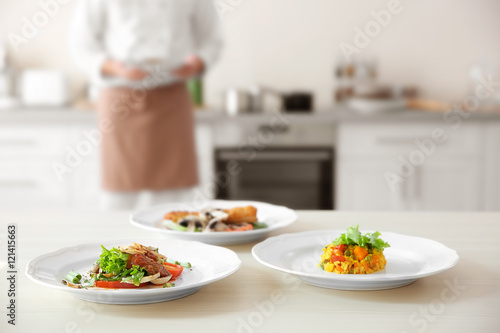 Foto op Canvas Klaar gerecht Plates with tasty dishes on kitchen table, closeup