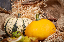Pumpkins, Straw And Jute Bag On Table