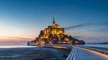 Mont Saint Michel Illuminated Architecture Panoramic Beautiful Postcard View At Dusk In Summer Low Tide From The Bridge With Reflection, France