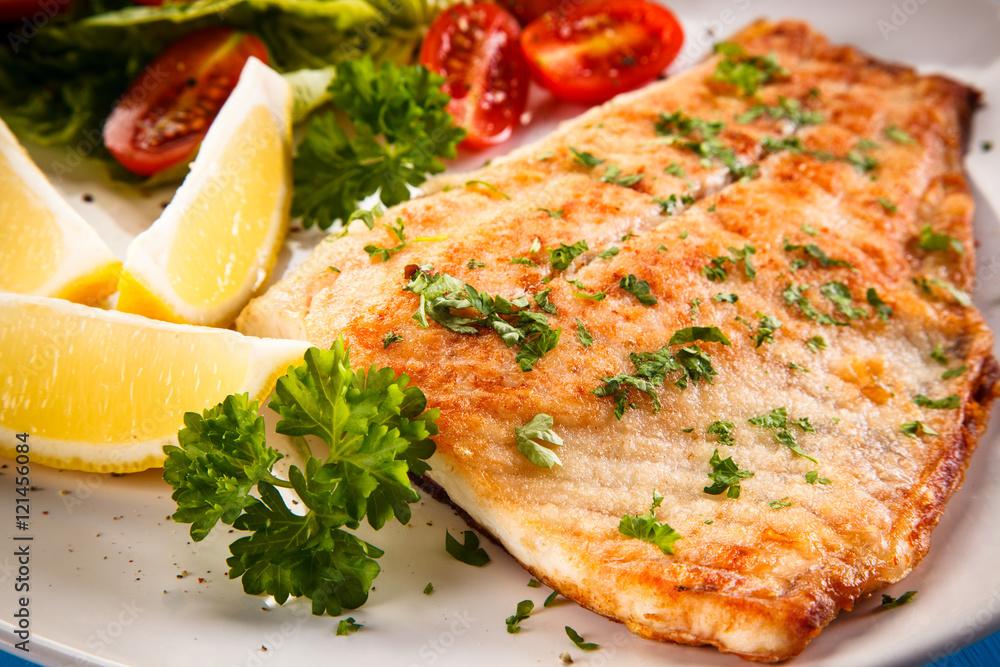 Fototapeta Fish dish - fried fish fillet baked potatoes and vegetables