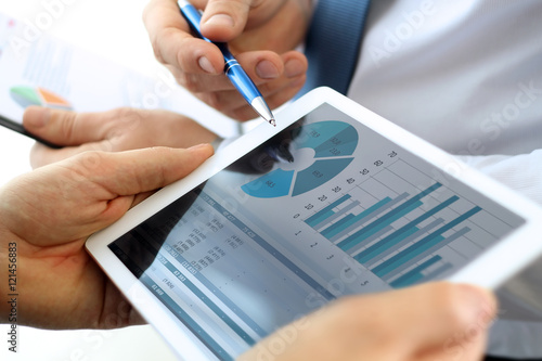 Photo Business colleagues working and analyzing financial figures on a
