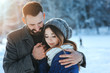 lifestyle shot of young happy couple walking in snowy forest, spending winter vacation outdoors