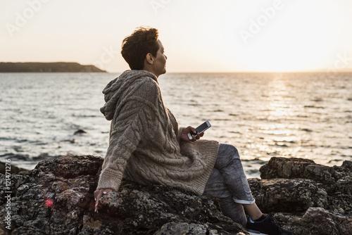 France, Crozon peninsula, woman with smartphone sitting on rocks at sunset