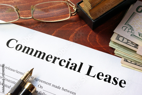 Fotografía  Commercial Lease agreement with money on a table.