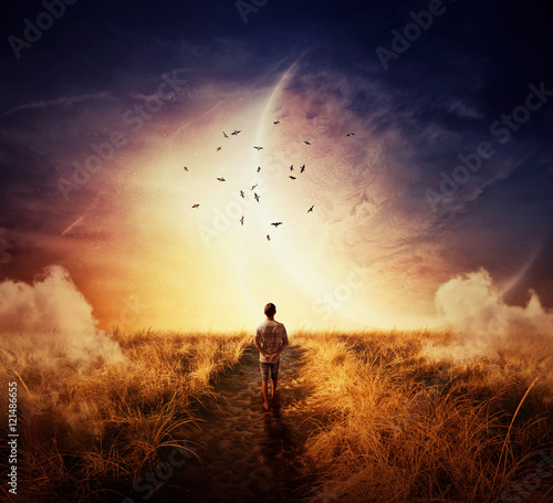 Fotografia Boy walking on a pathway with a relax mood, following a group of birds on the space horizon