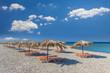Straw umbrella on a sandy beach in Greece.
