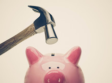A Sad Pink Piggy Bank Is About To Be Hit By A Hammer In Old Vintage Tone / Financial Problem