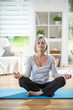 a pretty retired woman who does yoga at home, she meditates
