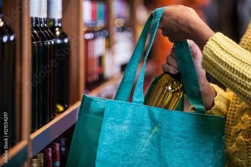 Vászonkép  Woman putting wine bottle in bag