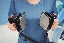 Mid Section Of Female Surgeon Holding Defibrillator