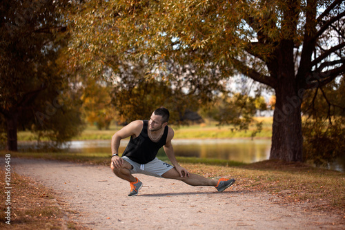 Fotografie, Obraz  Energetic young man do exercises outdoors in park to keep their bodies in shape