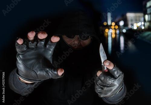 Valokuvatapetti Nachts in einer Stadt begeht ein Räuber einen Überfall