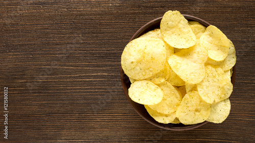 Fotografía  Potato chips in bowl on a table, top view.