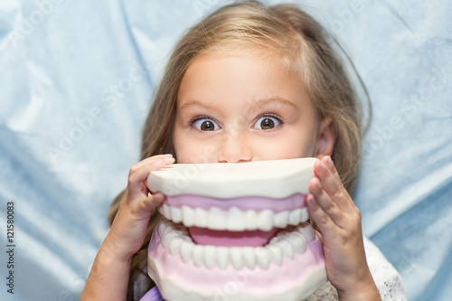 Fotografie, Tablou  Dentist curing a child patient in the dental office in a pleasant environment