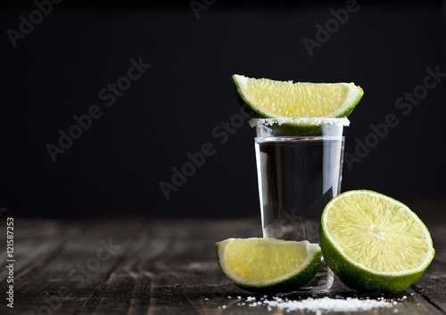 Fotografie, Obraz  Tequila silver shot with lime slices and salt on wooden board