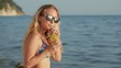 Girl in bikini drink juice through a straw. woman at the sea.