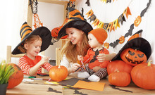 Family Mother And Children Decorate Home For Halloween