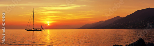 Photo sur Toile Mer coucher du soleil Panoramic view of Sailing at sunset with mountains