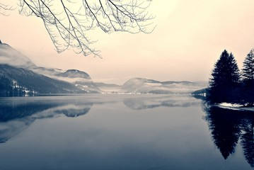 Fototapeta samoprzylepna Snowy winter landscape on the lake in black and white. Monochrome image filtered in retro, vintage style with soft focus, red filter and some noise; nostalgic concept of winter. Lake Bohinj, Slovenia.