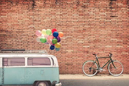 Fotobehang Fiets Vintage style photo card - classic car (vintage van) in city with colorful balloon on roof parked on road in urban. concept of love in summer and wedding, honeymoon.
