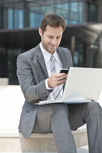 Businessman Multitasking While Working Outdoors