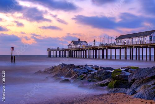 Fototapeten Sunrise at Southwold Pier with stone groynes, UK