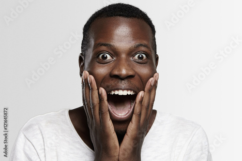Fotografie, Tablou  Shocked African student or employee looking at camera in full disbelief, hands on cheeks, mouth wide open, surprised with some unexpected news or big sale prices