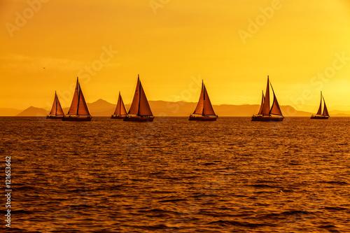 Staande foto Zeilen Regaty jachtów na morzu podczas zachodu słońca