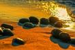 Kamyki na morskim brzegu w ciepłych promieniach zachodzącego słońca