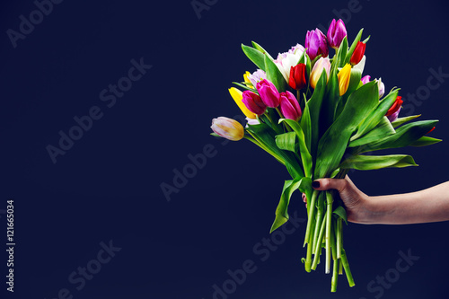 Fotografía  woman's hand gives a bouquet of tulips