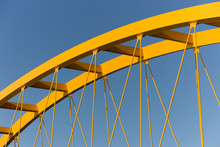 Yellow Bridge Against A Steel Blue Sky Showing Beams, Girders, Columns And Cables
