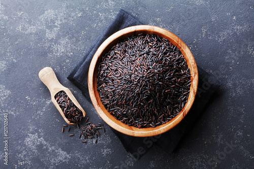 Black rice in wooden bowl on a dark table top view