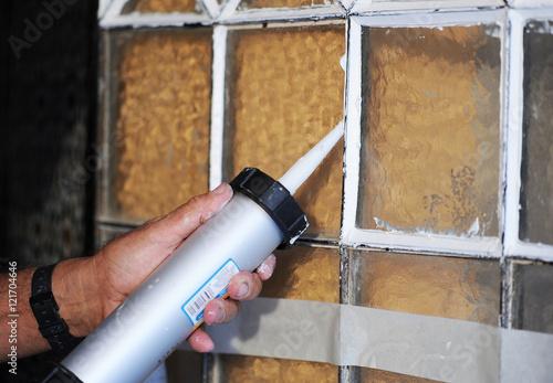 Fotografía  Cristalero colocando los cristales de una puerta antigua con pistola de masilla