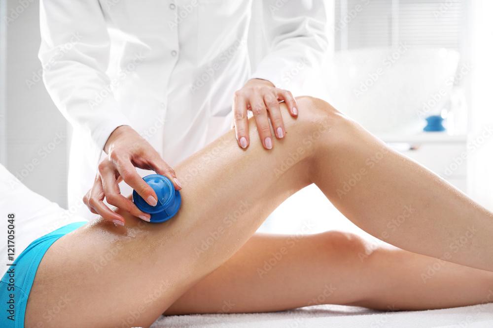 Fototapeta Manualny drenaż limfatyczny. Kosmetyczka masuje uda kobiety gumowymi bańkami do masażu.