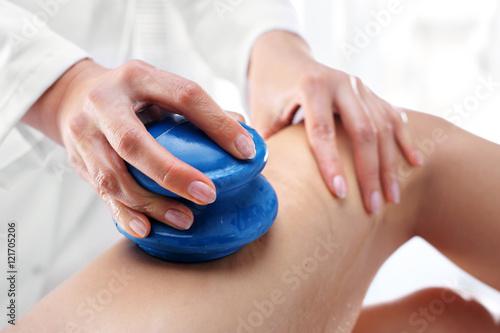 Masaż uda bańką chińską. Kosmetyczka masuje uda kobiety gumowymi bańkami do m...