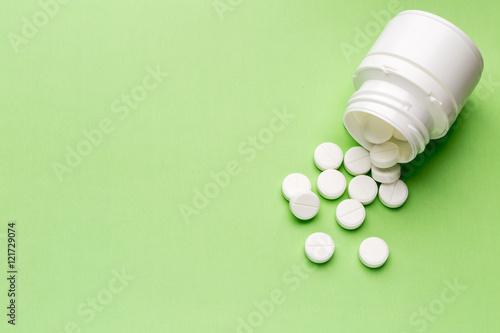 Fotografia  Round white pills and plastic pill bottle