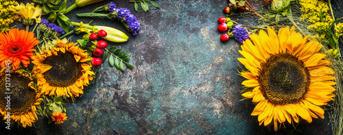 Floral decoration with sunflowers and fall flowers and leaves on dark vintage background, top view, banner, frame