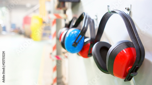 Canvas Print Row of Ear Defenders hung up in a factory with copy space