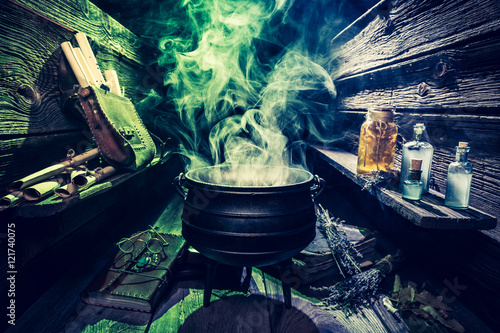 Photo  Magical witcher cauldron with scrolls, books and potions for Halloween
