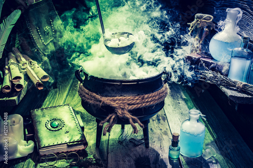Fotografie, Obraz  Mysterious witch pot with blue potions and books for Halloween
