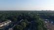 Flying over sport camp 4k aerial video. Skateboard ramp in forest park. City landscape in the background