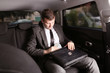 Businessman holding case with money in a car.