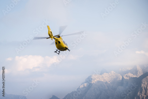 Tuinposter Helicopter Medical rescue helicopter in air. Italian Dolomites.