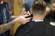 """Close-up back view of handsome young bearded man getting trendy haircut in modern barbershop. Cool male hairstylist with tattoo """"born barber"""" serving client. Indoors shot"""