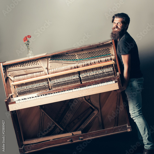 Plakat brodaty mężczyzna próbuje przenieść drewniany fortepian z różą