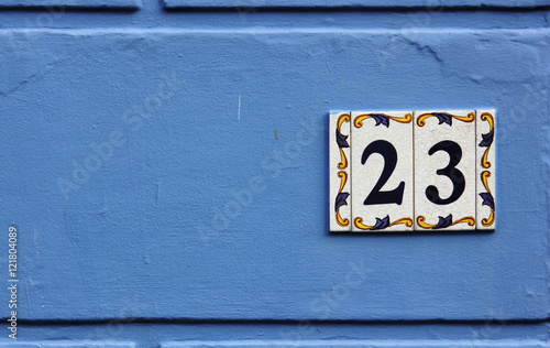 Fotografia  Ornate number 23 on a ceramic tile on a blue background