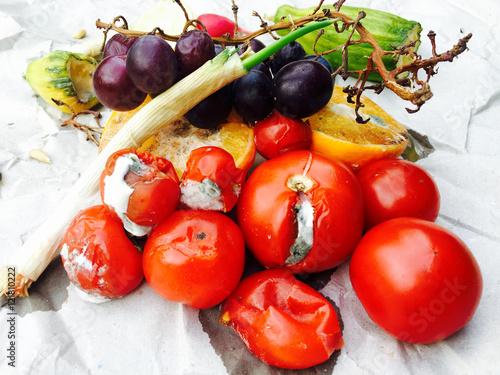 Valokuva  Verschimmelte Tomaten und Obst auf grauem Papier